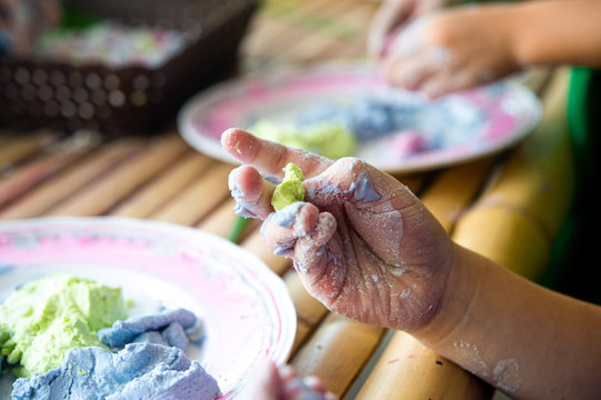 Closeup messy kid hand with natural colorful rice flours in pink plate, prepare to make most popular Thai sweetmeat dessert on bamboo table