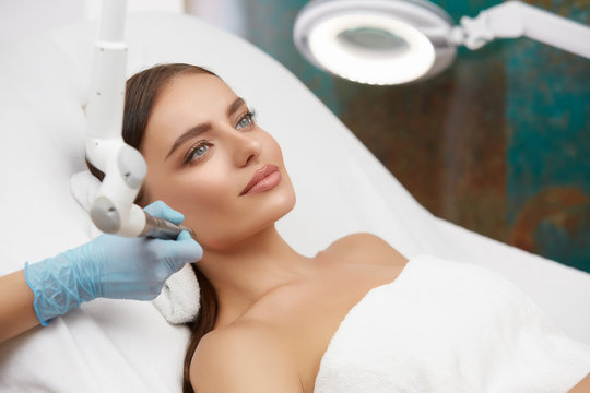 Cosmetology. Closeup Of Female Face having facial treatment in beauty salon. Cosmetic procedures in spa clinic.
