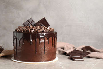 Freshly made delicious chocolate cake on marble table against grey background. Space for text