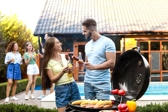 Young man and woman with grilled sausages at barbecue party outdoors