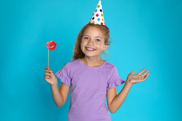 Happy girl with photo booth props on blue background. Birthday celebration