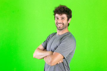 Crazy young man posing, believed expression on green background