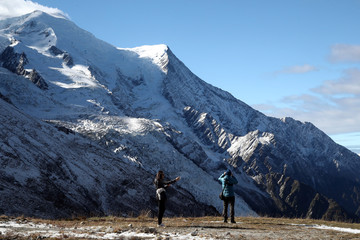 People take pictures of the Bossons glacier in the Mont-Blanc massif on a sunny autumn day in Chamonix