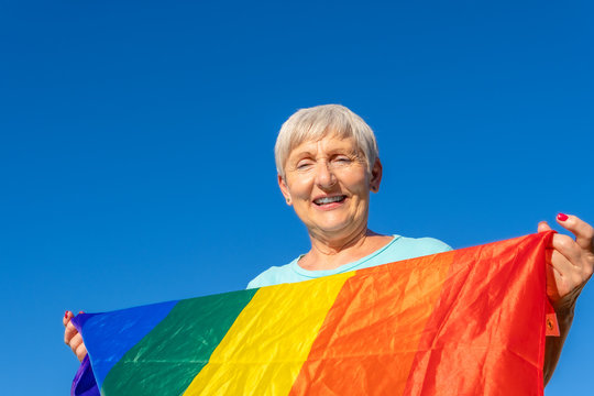 smiling senior woman with lgbt flag on blue background