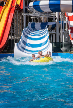 Happy family at the bottom of striped waterslide