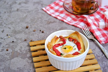 Breakfast, baked egg with cheese, sweet pepper and bread in a white portion form on a gray concrete background.