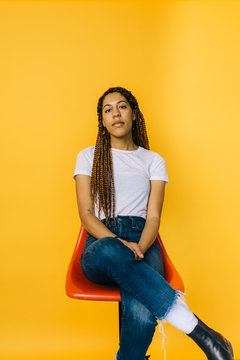 A portrait of a black woman in a plain white tee sitting on a stool in front of a orange backdrop