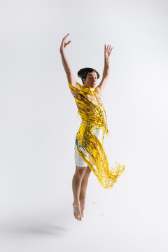 Male dancer jumps and spins around shiny gold streamers
