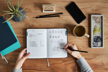 Overhead shot of a small business owner drawing in notebook