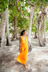Beautiful young woman walking among palm trees in Tahiti