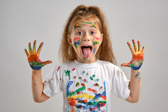Little girl in white t-shirt is posing standing isolated on white and gesticulating with her painted in different colors palms. Art studio. Close-up.