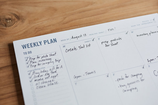 Overhead shot of a weekly planner on a wooden desk