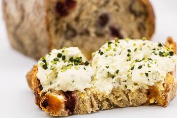 Tartine de fromage de chèvre frais aux fines herbes ail et échalotes ciselés sur une tranche de pain aux céréales et fruits secs arrière plan avec la miche de pain complete- isolé fond blanc studio
