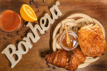 Pain au chocolat et croissant pur beurre, viennoiseries dans un panier en osier artisanal avec le mot bonheur sculpté dans un morceau de bois sur une table en bois avec un pot de miel et jus de fruit