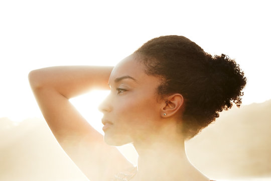 Portrait of mixed race woman backlit by the sun at the beach