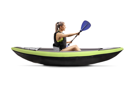 Young woman in a kayak wearing a safety vest and holding a paddle