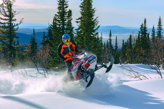 A man is riding snowmobile in mountains. Beautiful morning light. jump on a snow bike. pilot on a sports snowmobile in a mountain forest. The concept of skidooking. Lifestyle is active in winter sport