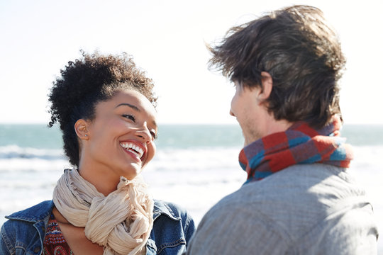 Mixed race couple smiling at each other at the beach