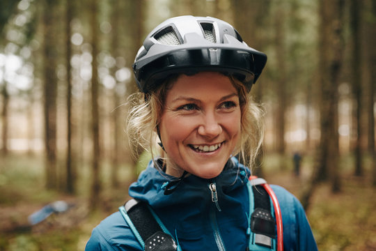 Smiling young woman ready for a mountain bike ride
