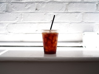 Cold brew coffee sitting on a white bench with a white brick background