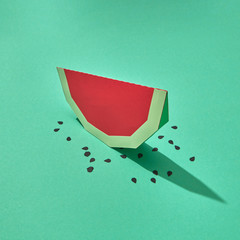 Handcraft paper slice of juicy watermelon with seeds on a green