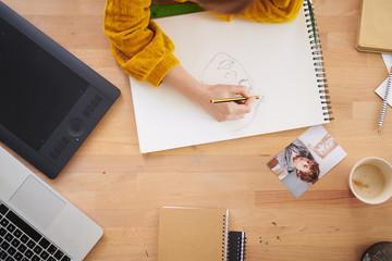 Woman at desktop drawing in album