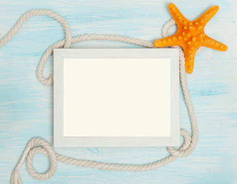 Sea background with frame and blue painted wood, rope, starfish, shells