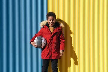 Portrait of happy boy holding soccer ball