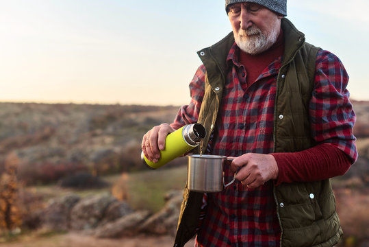 Eldery tourist man with gray hair and beard in plaid shirt drinking tea from a thermos to an iron mug against the background of the gorge and stones