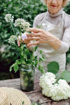 Crop senior woman collecting bouquet in vase
