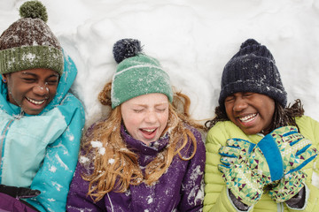 Laughing Black and Caucasian Girls in Snow