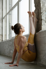 Young woman stretching near wall