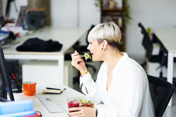 Laughing woman enjoying meal in office
