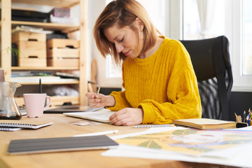 Stylish woman with art notepad at table