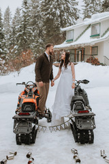 Wedding Couple Posed with Snowmobiles at Winter Wedding