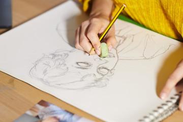 Woman erasing graphic portrait with pencil