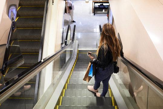 Faceless female shopping center escalator.