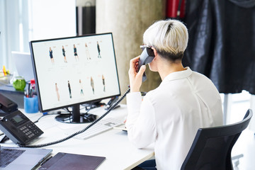 Woman using computer and speaking on phone