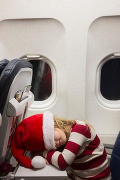 Girl wearing Santa hat sleeping on airplane