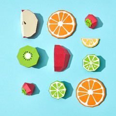 Pattern made of handmade craft pieces of apple, orange, lime, lemon, kiwi and strawberry on a blue background with copy space. Ingredients for Fruit Salad. Flat lay