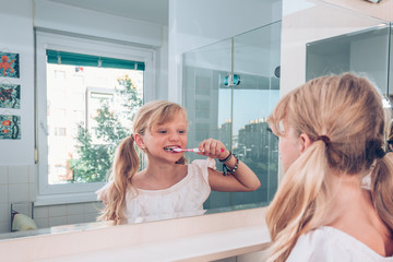 lovely blond child brushing her healthy teeth in the bathroom in front of the mirror