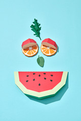 Smiling face made of paper pieces of watermelon, orange, apple and arugula leaves and mint on a blue background with copy space. Handcraft creative composition. Flat lay