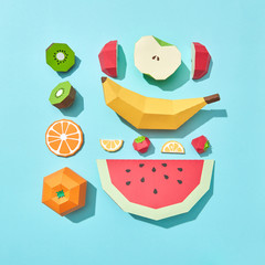Fruit made from paper. Hand crafted sliced kiwi, apples, strawberries, watermelon and lemon, banana on a blue background with space for text. Ingredients for Fruit Dessert. Flat lay
