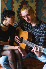 Young Couple Playing Acoustic Guitar at Home