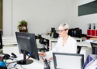 Contemporary businesswoman using computer in office