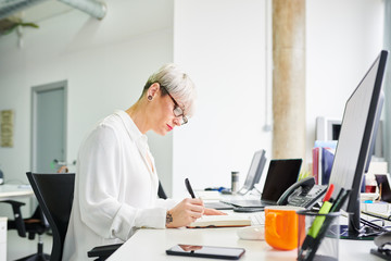 Stylish woman with notepad at desk