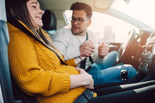 Pregnant woman starting to feel pain and contractions while her worried husband driving a car. She is ready to give birth in a car.
