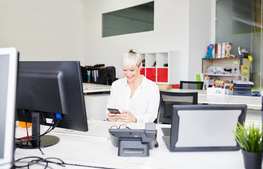 Smiling woman using phone in office
