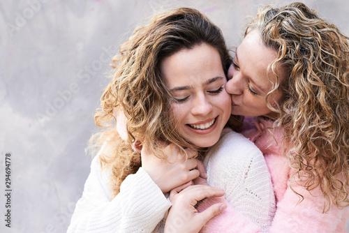Mother kissing daughter portrait.