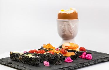 Mouillettes de pain noir au charbon et produits de la mer avec oeufs de lump saumon fumé et gambas beurre et aneth pour oeuf à la coque sur un plateau en ardoise - isolé sur fond blanc studio